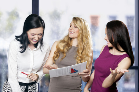 good business: Three women at workplace joking and laughing