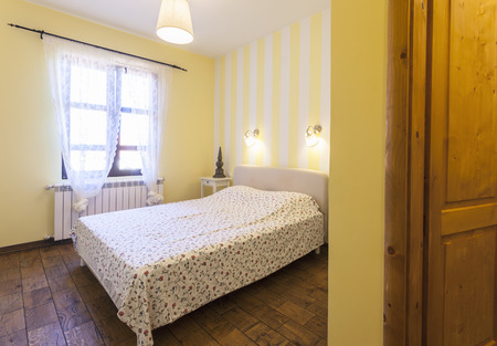 Interior of a simple bedroom with yellow walls photo