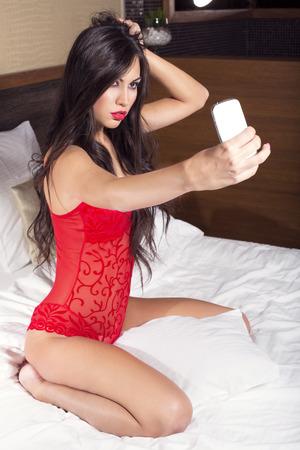 mujer sexy: Mujer atractiva en ropa interior roja hablar Autofoto Foto de archivo
