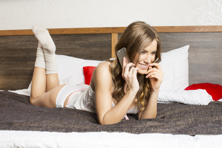 Cute young woman in bed on the phone photo