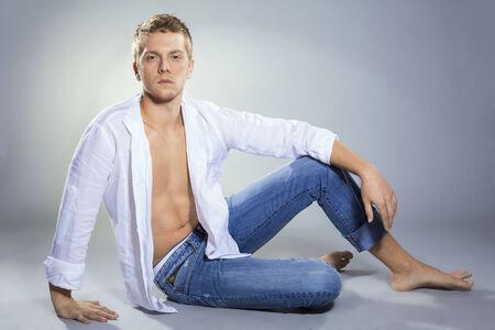 pies masculinos: Hombre rubio hermoso en la camisa desabotonada y jeans Foto de archivo