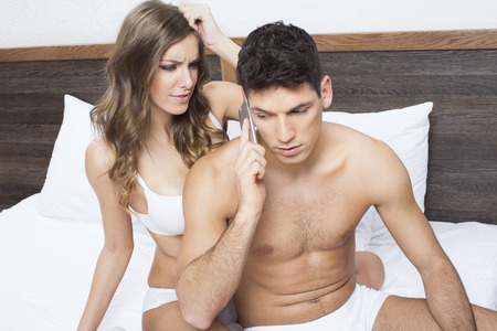 sexy couple in bed: Young woman angry about her boyfriend talking on the phone Stock Photo