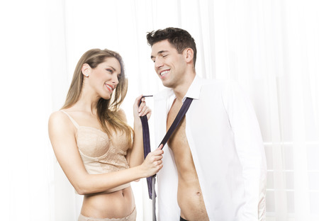 woman undressing: Happy young couple taking their clothes off Stock Photo