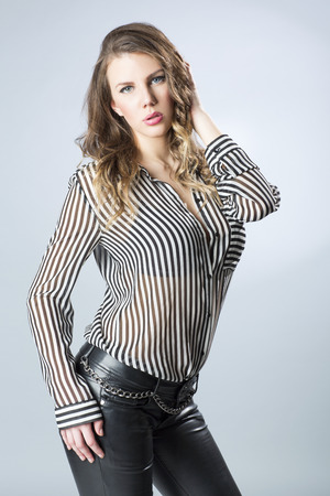 striped shirt: Attractive young woman in leather pants and shirt