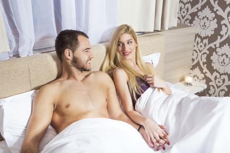 mujer enamorada: Pareja feliz en la cama