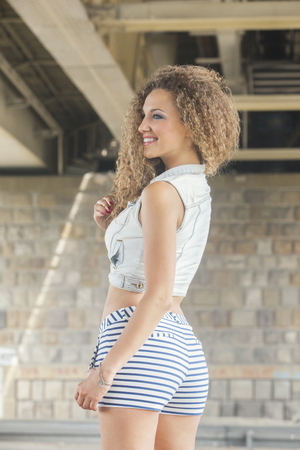 denim shorts: Woman with big curly hair in denim vest and short shorts