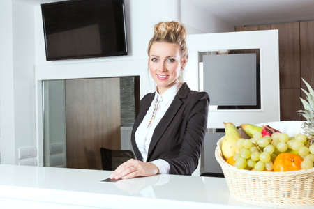 hotel receptionist: Beautiful hotel receptionist handing out key Stock Photo
