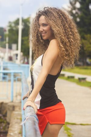 hair curly: Outdoors portrait of a cheerful woman with curly hair Stock Photo