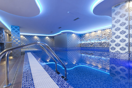hotel with pool: Indoors pool with colorful lights at spa center