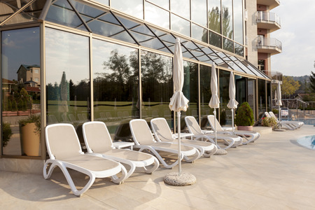 lounge chairs: Poolside lounge chairs in front of hotel