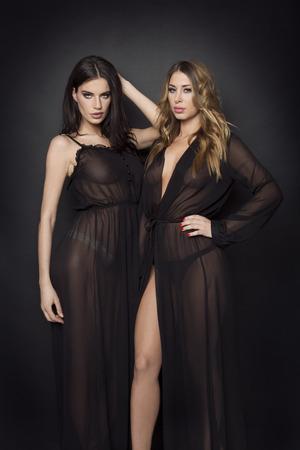 Twee vrouwen in zwarte doorschijnende jurken