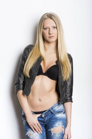 Portrait of a young woman in leather jacket and bra Stock Photo