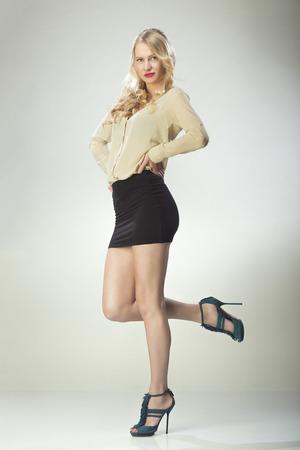 falda corta: Mujer joven que presenta en falda corta negro y una blusa Foto de archivo