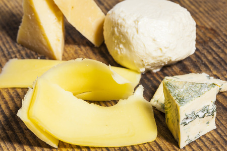 different types of cheese: Different types of cheese on a wooden board Stock Photo