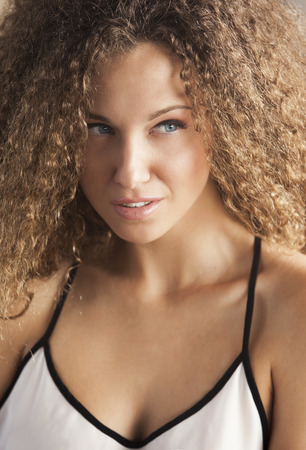 spaghetti strap: Portrait of a beautiful woman with curly hair Stock Photo