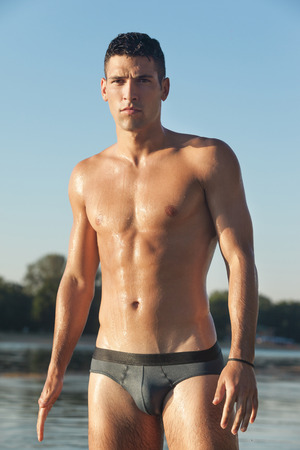 beach hunk: Muscular man in swim briefs getting out of water