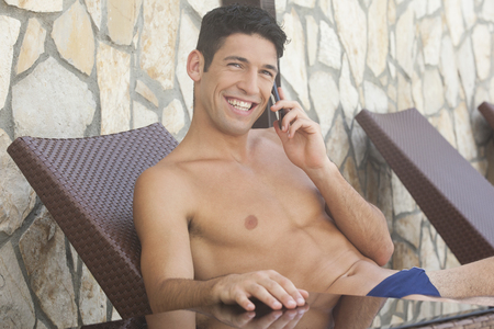 briefs: Man in swim briefs sitting in lounge chair and talking on the phone Stock Photo