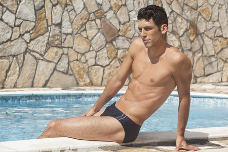briefs: Handsome man in swim briefs by the pool