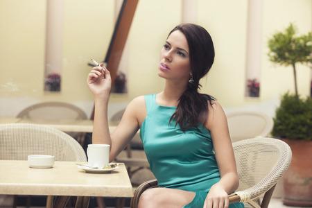 persona fumando: Mujer bonita de fumar en un caf� al aire libre Foto de archivo