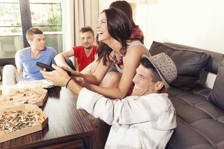 pareja viendo tv: Amigos que se divierten en el hogar, la lucha por el control remoto