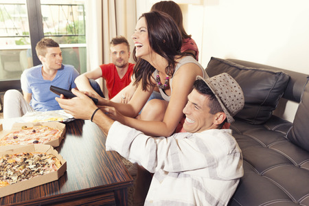 Friends having fun at home, fighting over remote control Stockfoto