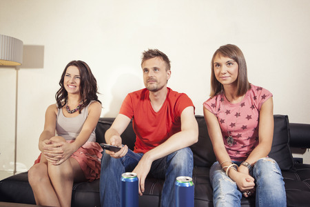 two women and one man: One man and two women sitting on couch watching TV