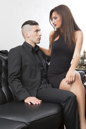 Attractive couple on leather sofa Stock Photo