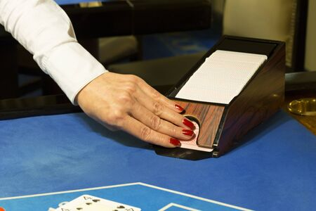 croupier: Croupier pulling out cards from box at blackjack table