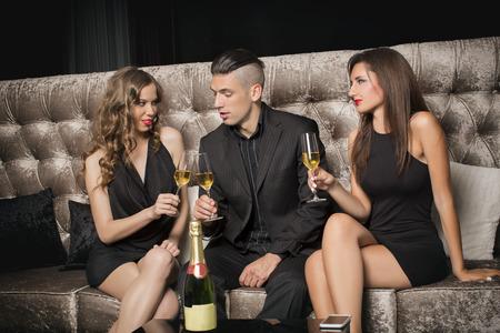 brindisi spumante: Un uomo e due donne a celebrare con champagne in discoteca