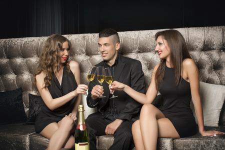 Een man en twee vrouwen vieren met champagne in nachtclub