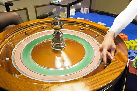 croupier: Croupier spinning the roulette wheel at casino