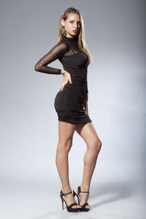 modelos posando: Mujer atractiva en vestido corto negro Foto de archivo