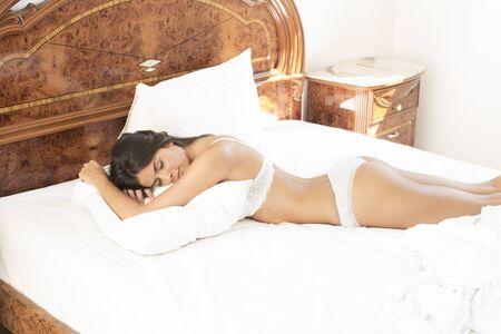 Beautiful woman lying in bed in the morning Reklamní fotografie