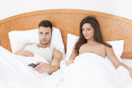 couple watching tv: Couple watching TV in bed