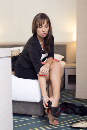 taking off: Woman in bedroom taking off shoes