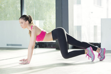 young women: Young woman exercising at the gym