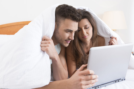 bed sheet: Young couple snuggled under the cover with laptop
