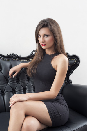 Elegant woman in black dress sitting on black sofa Stock Photo
