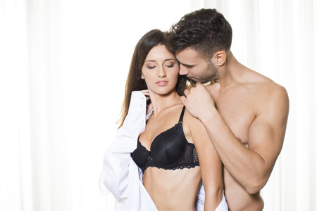 undressing: Attractive couple in embrace