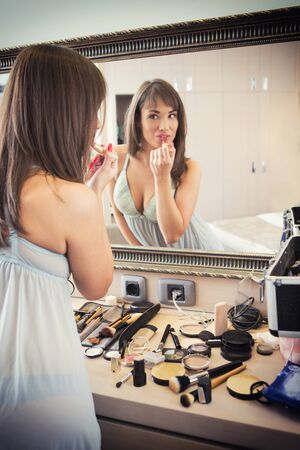 woman mirror: Cheerful young woman in front of mirror applying make-up Stock Photo