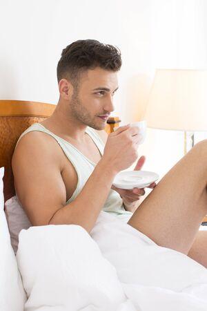 hombre tomando cafe: Hombre guapo beber café en la cama