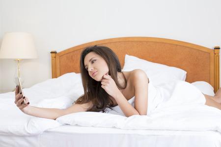 jungen unterw�sche: Sch�ne junge Frau, die im Bett selfie