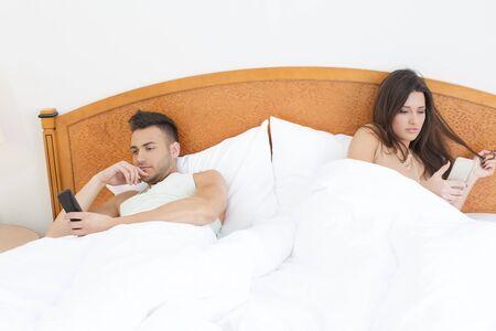 couple bed: Couple au lit, � la fois en utilisant les t�l�phones