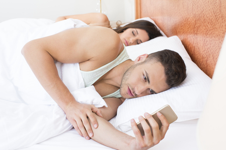 Man texting in bed while his girlfriend in asleep Stock Photo