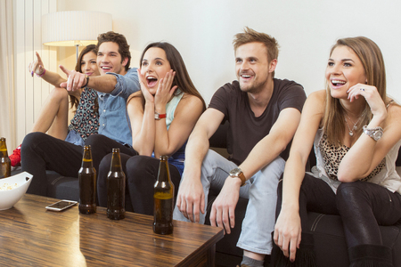 college dorm: Group of friends watching TV match and cheering Stock Photo
