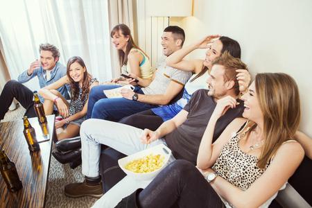 家でテレビを見ている友人のグループ 写真素材