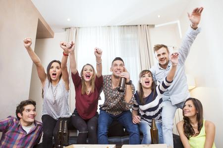 Groep vrienden TV kijken match en juichen Stockfoto - 50767582