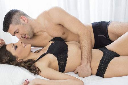young woman in underwear: Attractive couple in bed Stock Photo