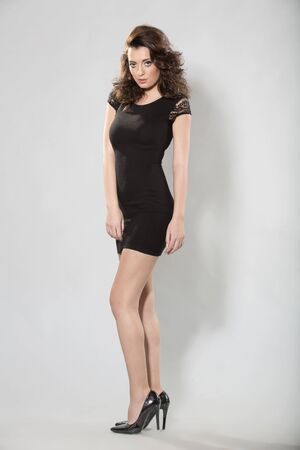 Beautiful young woman posing in black dress Stock Photo