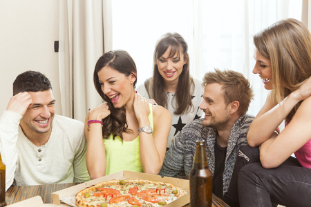man drinking beer: Group of friend having beer and pizza at home Stock Photo